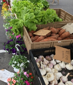 Garlic, potatoes and greens line this produce stand at a western Pennsylvania farmers market.